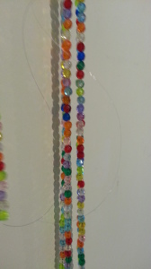 "Close up from the installation process of Jack Giesen's ""Reaching"" beadwork installation. Several strands of multicoloured beads hanging vertically against a wall."