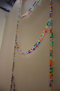 Rungs of a ladder of multicoloured beads care strung from a wall. Strings of horizontal beads bow under their own weight horizontally across the piece.