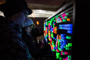 "Attendees interact with a large-scale ""light-brite""-esque installation at a Night/Shift event"
