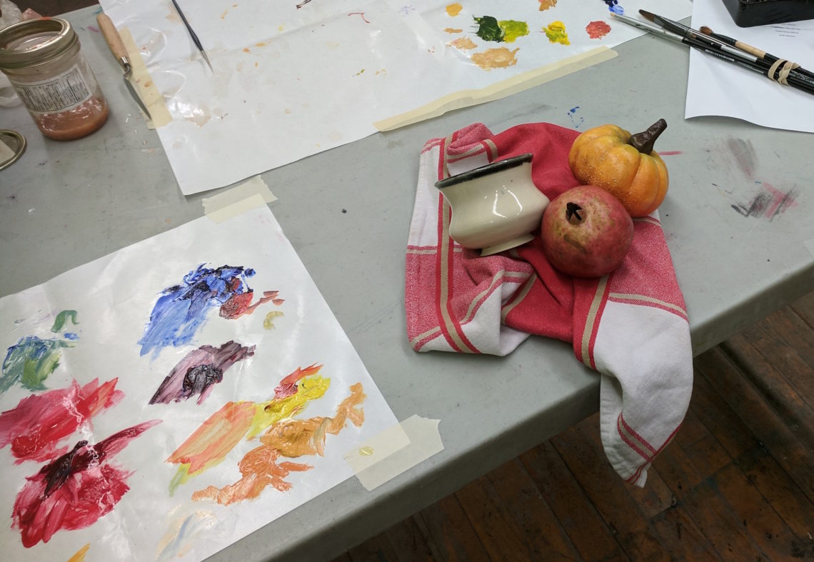 A grey table holds Jack Giesen's messy oil painting palette from October 3, as well as the Harvest still life, which sits on a red and white towel.