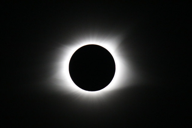 """Total Eclipse of the Sun"" by Mark Moschell, a photo with a mostly black background, a pure black circle at the centre, and a ring of light all the way around it."