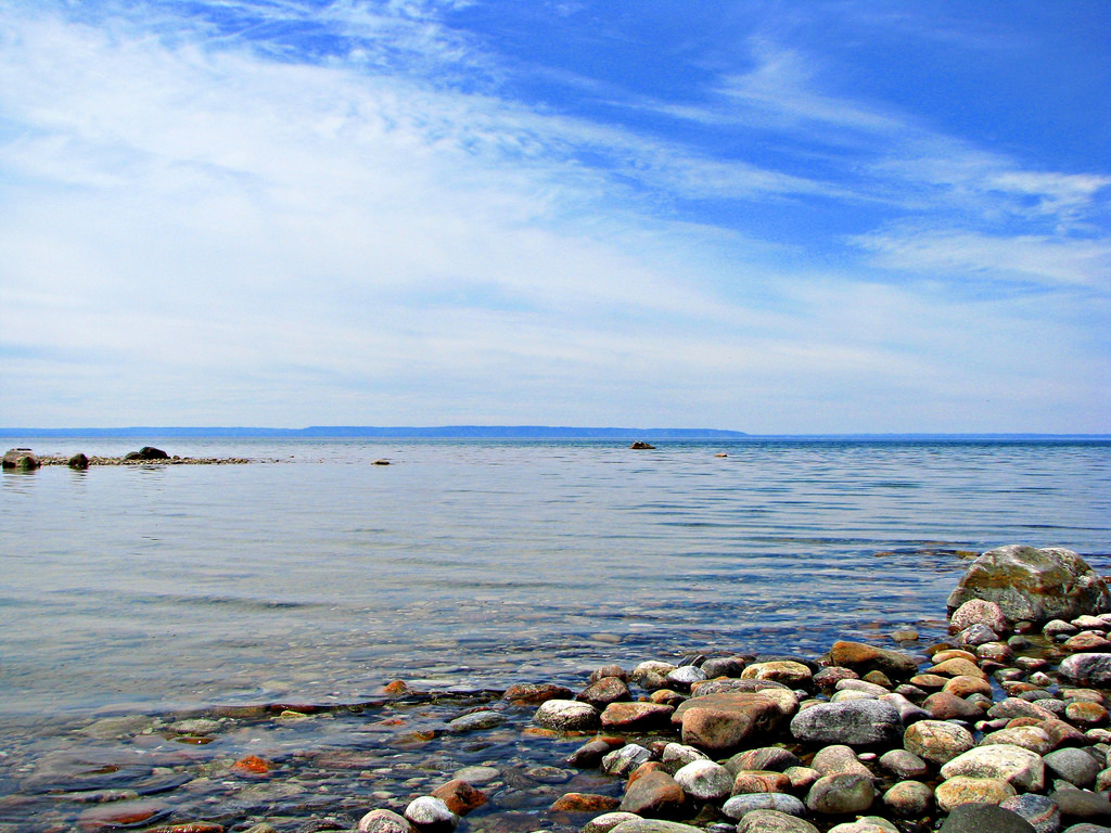 A blue sky with wispy clouds over a stony beach near the township of Tiny, Ontario.
